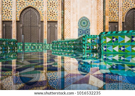 view of Hassan II mosque's big gate reflected on fountain water - Casablanca - Morocco #1016532235