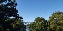 View of Henry Hudson bridge from Inwood Hill Park between the tree tops on a clear, sunny day.