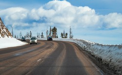 View of highway ascending toward mountain pass; blue sky and beautiful clouds in background; winter in Colorado