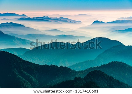 View of Himalayas mountain range with visible silhouettes through the colorful fog from Khalia top trek trail. Khalia top in himalayan region of Kumaon, Uttarakhand, India. #1317410681