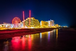 View of hotels and rides along the boardwalk at night from the fishing pier in Daytona Beach, Florida.