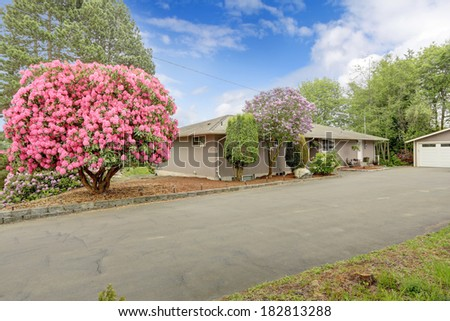 View of house with long deck, concrete stairs and beautiful blooming bushes of house with garage and driveway. Beautiful blooming trees.