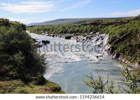 View of Hraunfossar series of waterfalls formed by rivulets streaming over a distance of about 900 meters and wide river with strong flow on a sunny summer day in Iceland, Europe