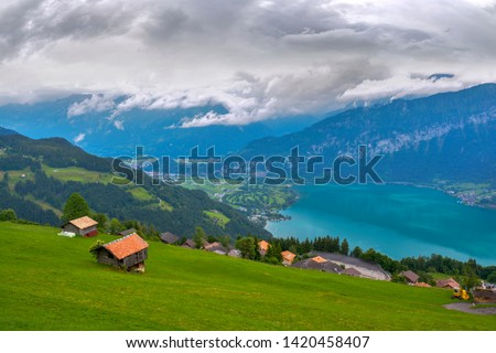 View of huts and Lake Thun (Thunersee) on the slope of the forest-covered mountains in the Swiss Alps under dramatic clouds on rainy day in Beatenberg, Switzerland