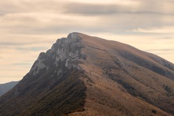 View of impressive Trem summit on Suva planina (Dry mountain), Serbia, cloudy, golden, morning sky and autumn colored forest trees on the steep cliffs