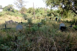 view of Indian grave yard with cross and grave stone on green grass