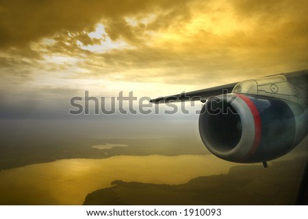 View of jet engine and wing a few thousand feet over the ground during sunset