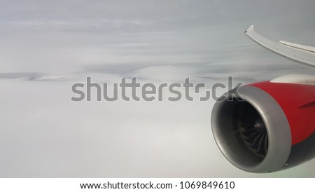 View of jet plane engine and wing from insight of the aircraft cabin window.  Overcast sky background.