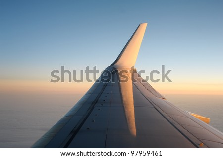 View of jet plane wing in clear evening sky.