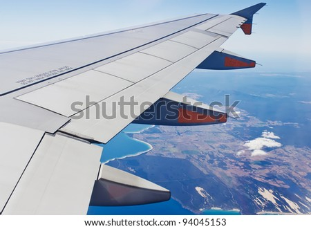 View of jet plane wing with cloud patterns and earth