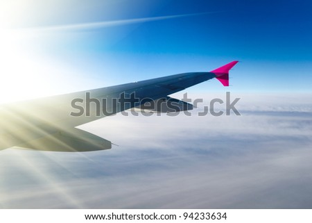 View of jet plane wing with sun