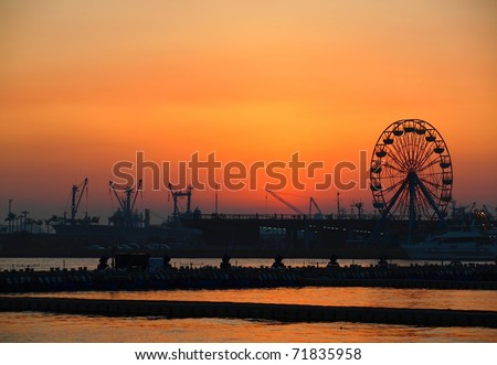 View of Kaohsiung Harbor at sunset with the silhouette of a small ferris wheel
