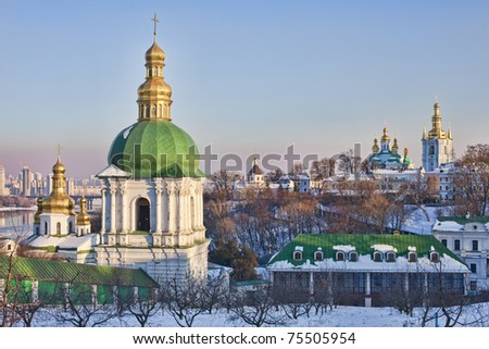 View of Kiev Pechersk Lavra Orthodox Monastery with church of Holy Cross and church of Nativity of the Holy Virgin in snow at sunset, Ukraine