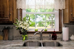 View of Kitchen sink, window view of backyard, curtains and flowers.  Two green tomatoes on window seal witing to ripe.  Beautiful designer gray/white/green granite countertop.