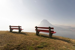 View of Lake Lugano in a foggy day, from the park San Michele, with two red empty benches.