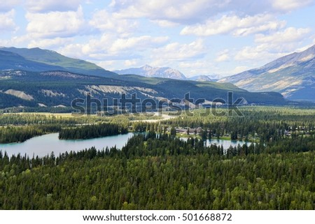 View of Lakes Surrounded by Evergreen Forests with Towering Rocky Mountains Set Against Dramatic Cloudy Sky #501668872