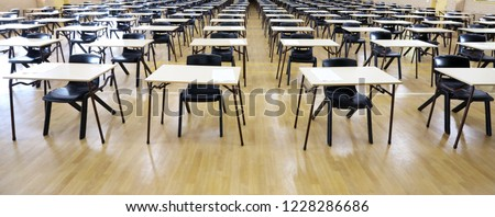 View of large exam room hall and examination desks tables lined up in rows ready for students at a high school to come and sit their exams tests papers.  #1228286686