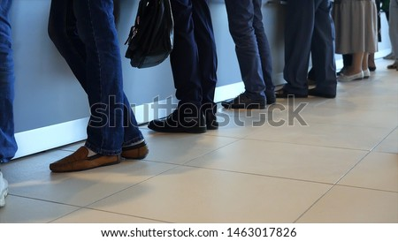 View of legs of customers standing n the modern office, getting served in the bank. Media. People are queuing for service in the department of a bank. Foto stock ©