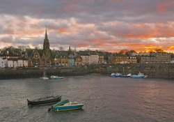 View of Leith area of Edinburgh, Scotland in the winter with red sunset and boats on the foreground