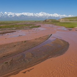 View of Lenin Peak nowadays Ibn Sina peak in the snow-capped Trans-Alai mountain range in southern Kyrgyzstan with colorful Kyzyl Suu river in the foreground