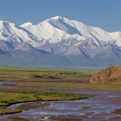 View of Lenin Peak nowadays Ibn Sina peak in the snow-capped Trans-Alai mountain range in southern Kyrgyzstan with Kyzyl Suu river in the foreground