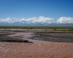 View of Lenin Peak nowadays Ibn Sina peak in the snow-capped Trans-Alay mountain range in southern Kyrgyzstan with Kyzyl Suu river in the foreground