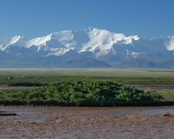 View of Lenin Peak nowadays Ibn Sina peak in the snow-capped Trans-Alay or Trans-Alai mountain range in southern Kyrgyzstan with Kyzyl Suu river in the foreground