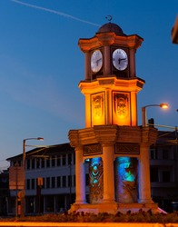 View of lighted small three storey clock tower decorated with columns and sculptures in center of Bursa in dusk, Turkey
