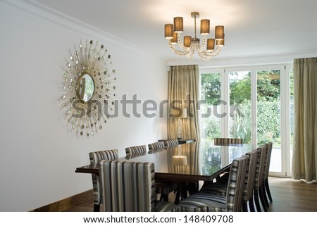 View of lit chandelier over the dining table with decorated art on wall at home