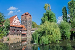 View of little island in Pegnitz river from the Maxbrücke bridge, in Nuremberg old city, Germany, Bayern, Deutschland.