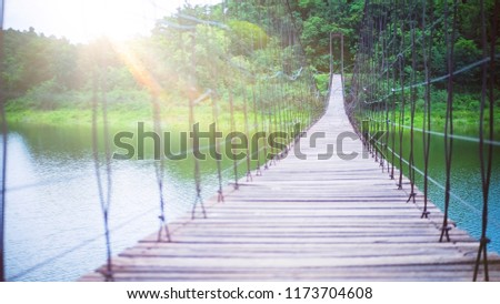 View of Long suspension wooden bridge over natural lake with sunlight flare at Kaeng Krachan National Park, Phetchaburi, Thailand