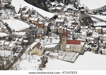 View of Luson (Alto Adige, Italy) village centre with snow and typical church seen from the mountains