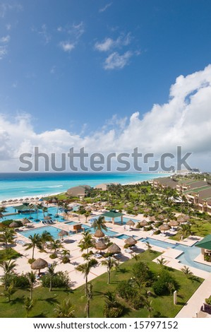 View of luxury tropical oceanfront resort with pools and lush landscaped grounds