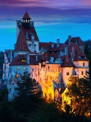 View of main romanian tourist attraction Bran Castle on cliff top on twilight.
