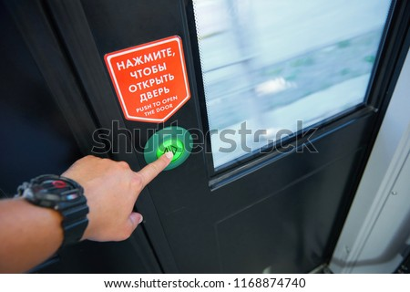 View of man hand pushing the door push button to make an unlock signal for local doors opening while train stops at a station. Passenger train interface buttons and light signals  #1168874740