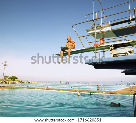 View of man reading the newspaper while sitting on a diving board, Cape Town, South Africa