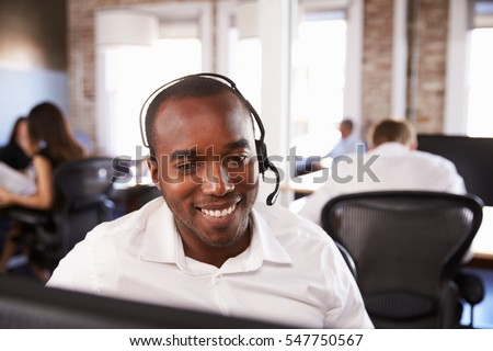 View Of Man Working In Busy Customer Service Department