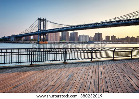 View of Manhattan Suspension Bridge Spanning the East River with View of Manhattan from Boardwalk in Waterfront Brooklyn Park, New York City, New York, USA
