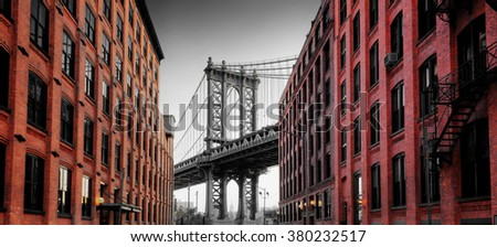 View of Manhattan Suspension Bridge Supportive Arch in Black and White Framed by Colorized Brick Buildings on Washington Street in Brooklyn, New York City, New York, USA