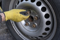 View of mans hands in yellow gloves screwing out wheel bolts.