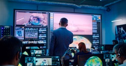 View of mature man in suit gesticulating and giving commands to operators while launching rocket with astronaut remotely in flight control station