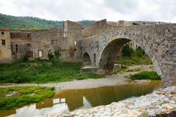 View of medieval stone arched bridge of Benedictine Abbey Sainte-Marie d'Orbieu in Lagrasse