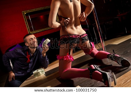 View of men offering money to a stripper on stage