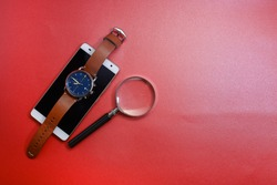 View of men wrist watch face with a note book and eye glasses at the back isolated on red background.  Beauty and fashion and prestige concept
