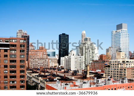 View of metropolitan city hirise skyscraper rooftops under a deep blue spring or summer sky. Upper East Side tall buildings viewed from above in Manhattan, New York City.