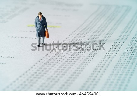 View of miniature toy, businessman walking on financial documents. Soft blue filter.