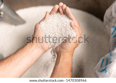 View of modern factory worker hands holding pile of white polymer pellets ストックフォト ©