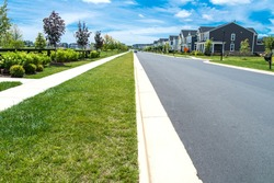 View of modern residential houses neighborhood street and asphalt road in Leesburg, Virginia. sunny flare day, fast-growing city lifestyle