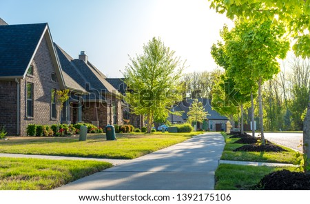 View of modern residential houses neighborhood street in Bentonville, Northwest Arkansas, sunny flare day, fast growing city lifestyle