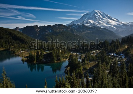 View of Mount Rainier on a clear blue day with a still mountain lake in the foreground and a dusting of snow in the lower hills